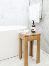 Side table with timber legs and a black and white tile attached to the timber top.